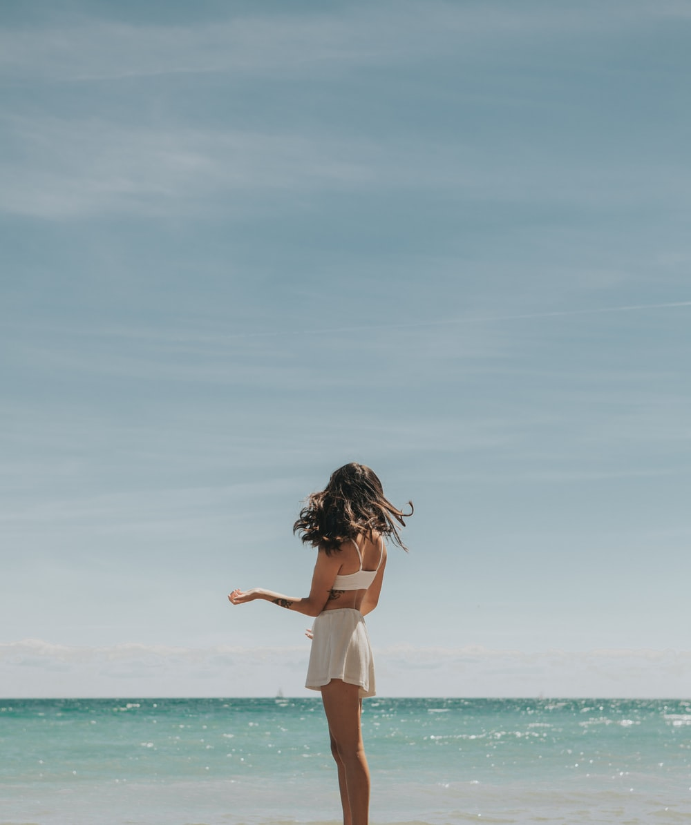 woman in white dress standing on seashore during daytime