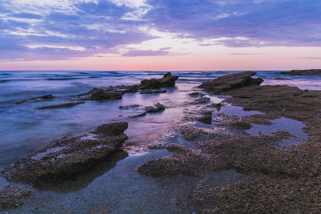 Black Rocks On Sea Shore During Daytime - unsplash