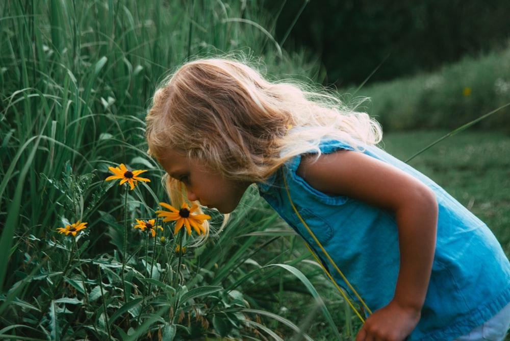 girl in blue sleeveless dress holding yellow flower