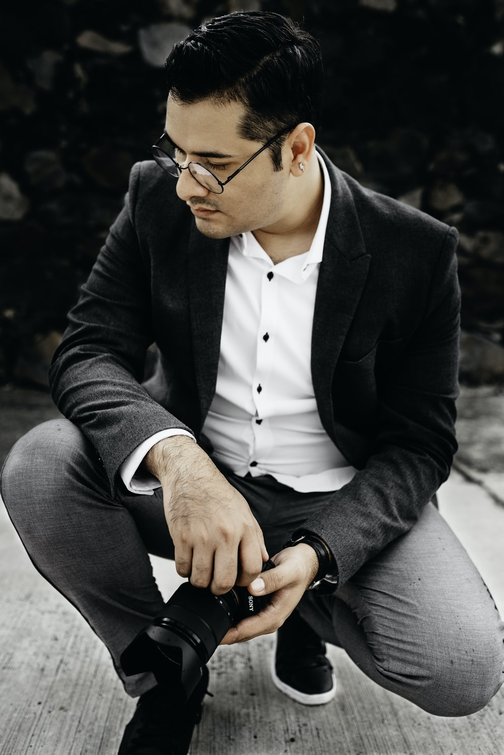 man in black suit jacket and gray dress pants sitting on gray concrete bench during daytime