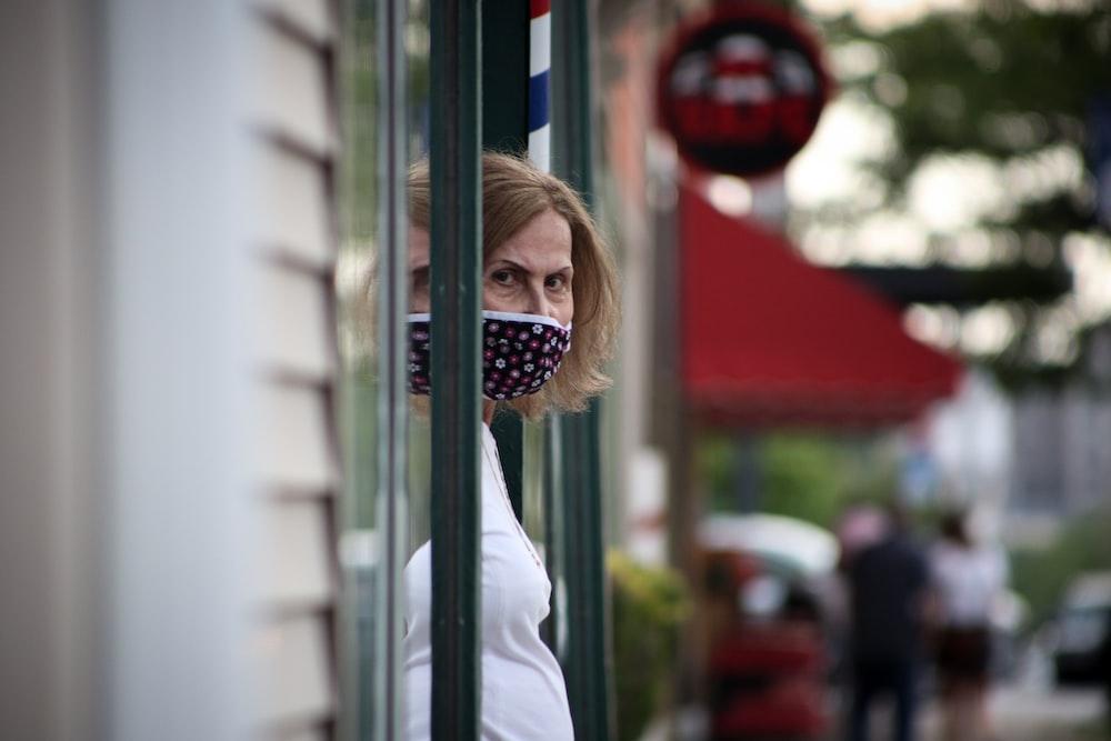 girl in white long sleeve shirt standing near glass window during daytime