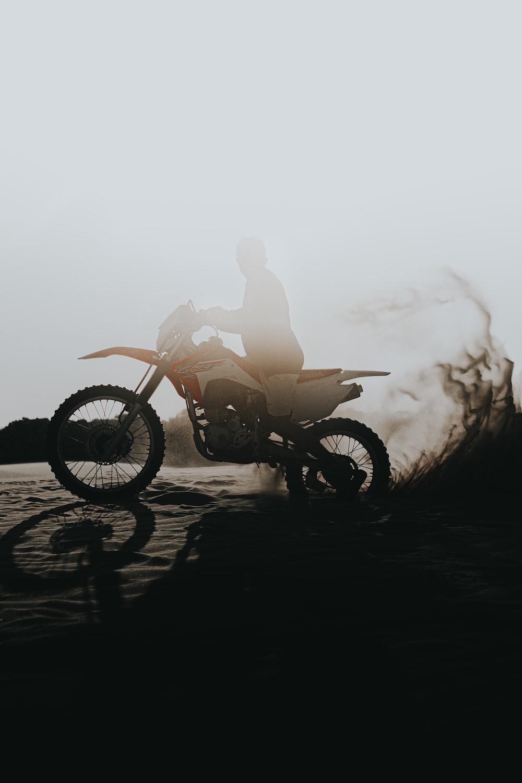 man riding motorcycle on beach during daytime
