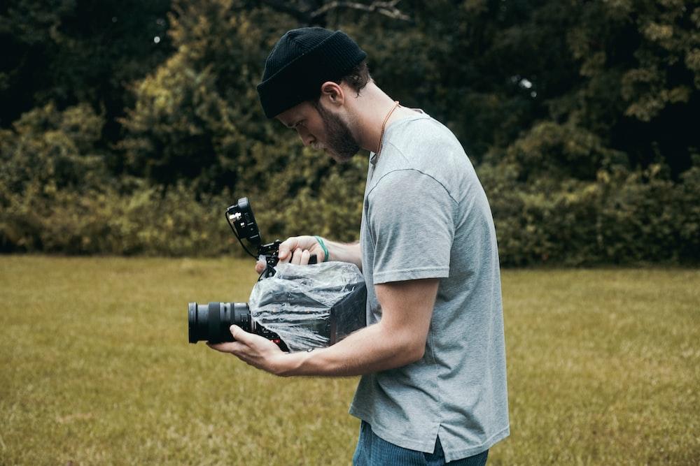 man in gray crew neck t-shirt holding black dslr camera during daytime