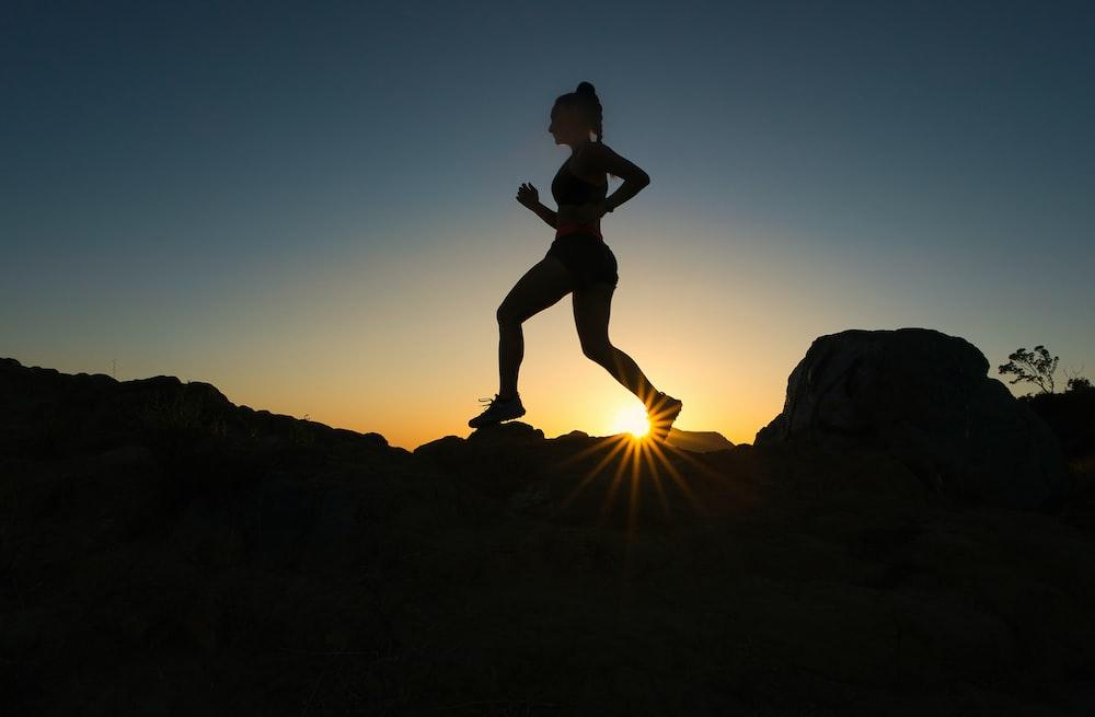 日没時に岩山にジャンプする男のシルエット