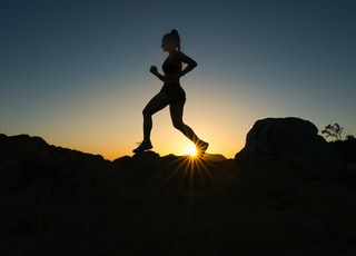 silhouette of man jumping on rocky mountain during sunset
