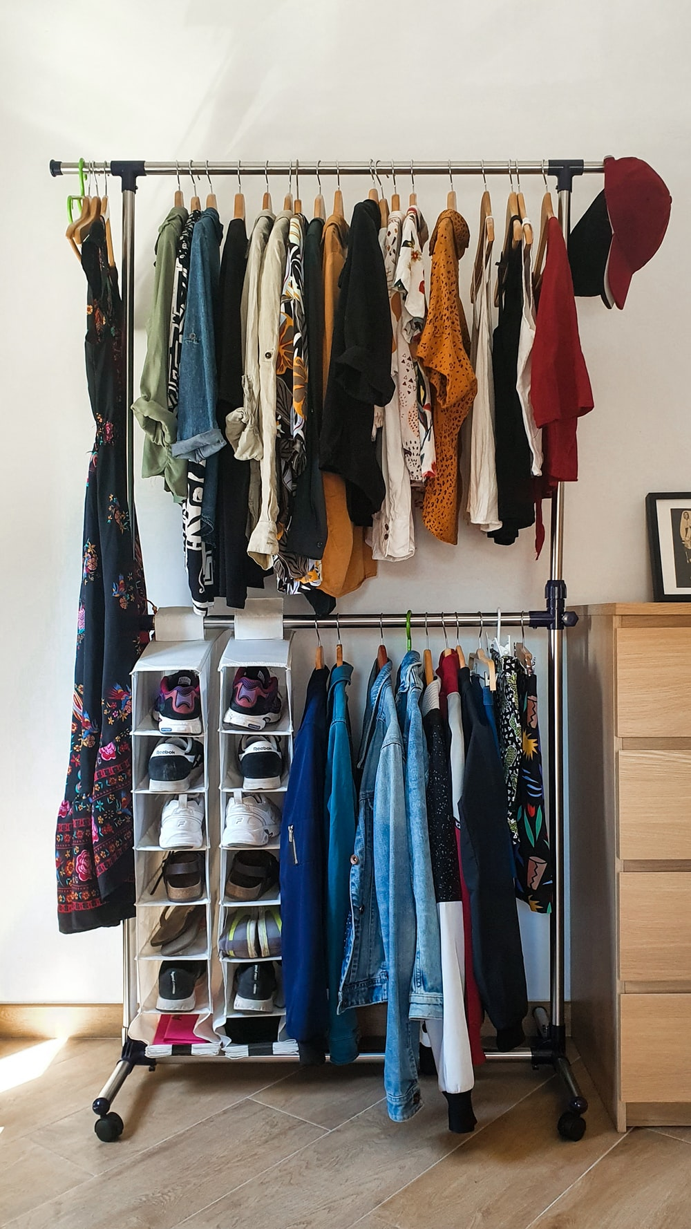 clothes hanged on brown wooden cabinet