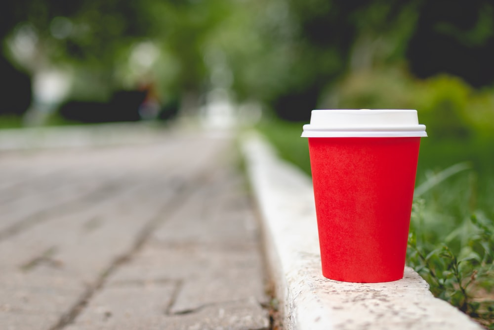 red and white plastic cup on gray concrete floor