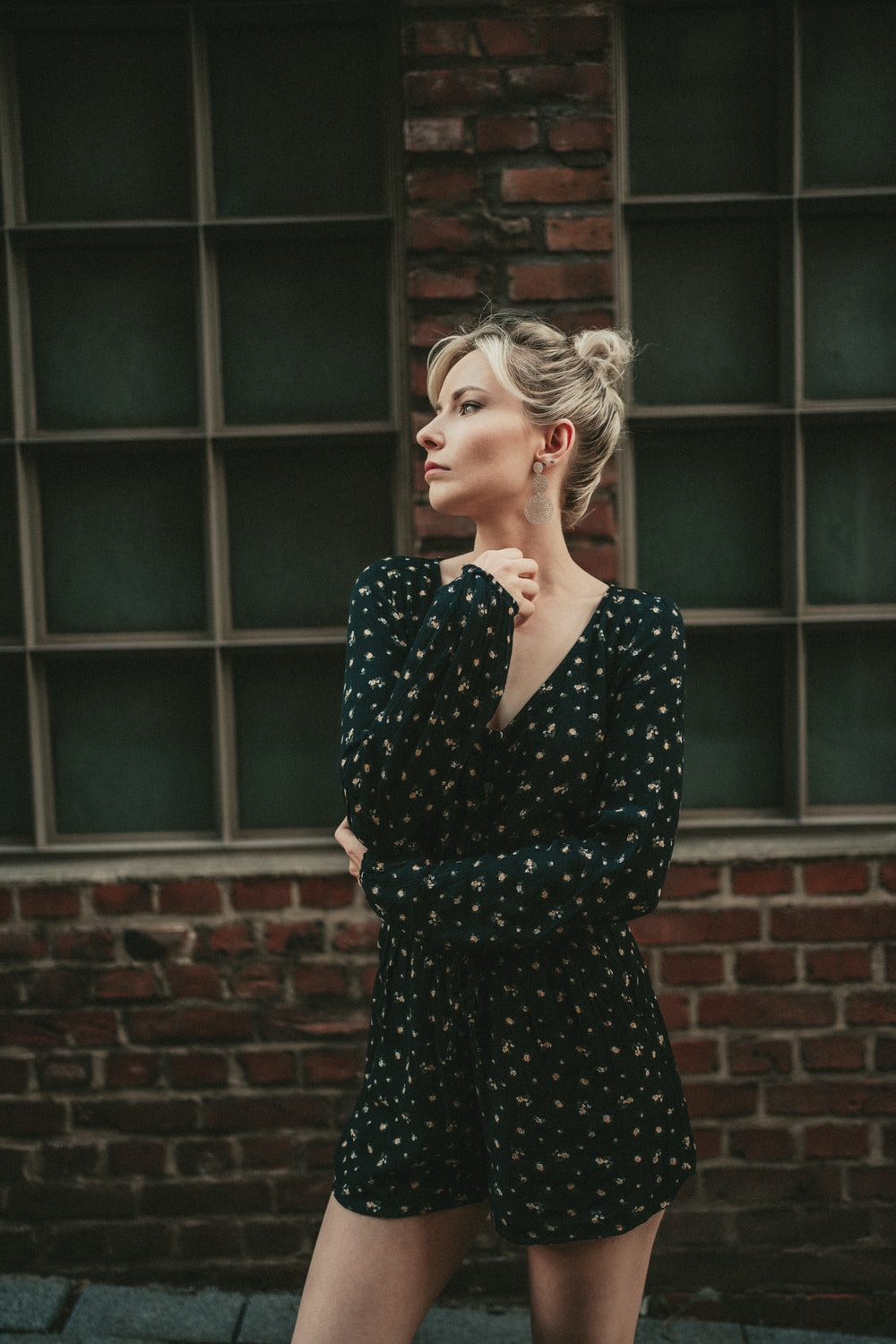 woman in black and white polka dot long sleeve dress standing near brown brick wall