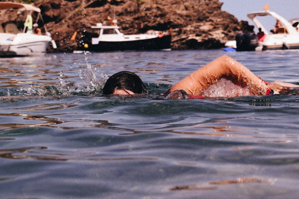 woman in black swimming goggles in water during daytime