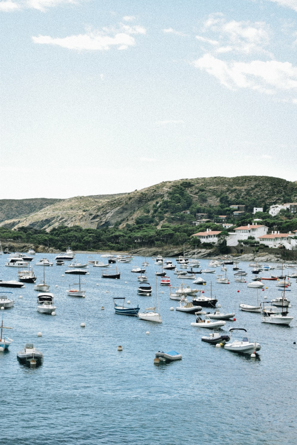 white boats on sea near green mountain during daytime