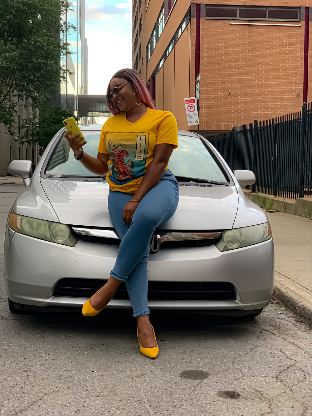 woman in yellow crew neck t-shirt and blue denim jeans leaning on silver car