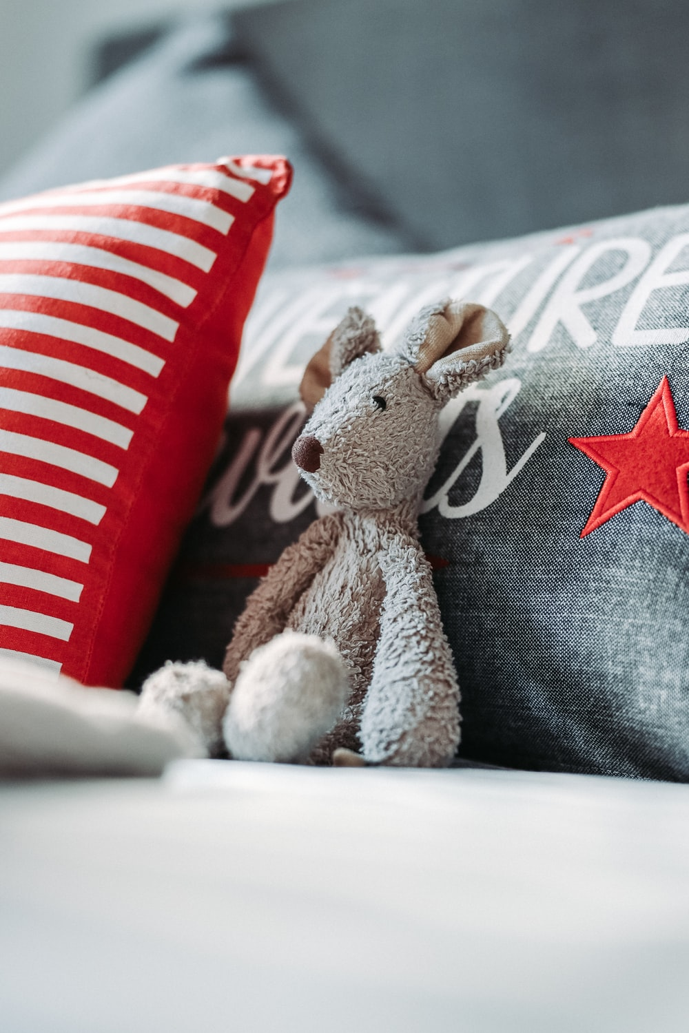 gray teddy bear on gray and white star print textile