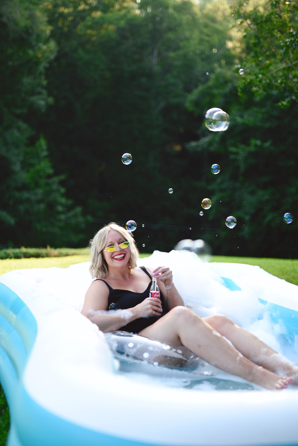 woman in black tank top lying on blue inflatable ring