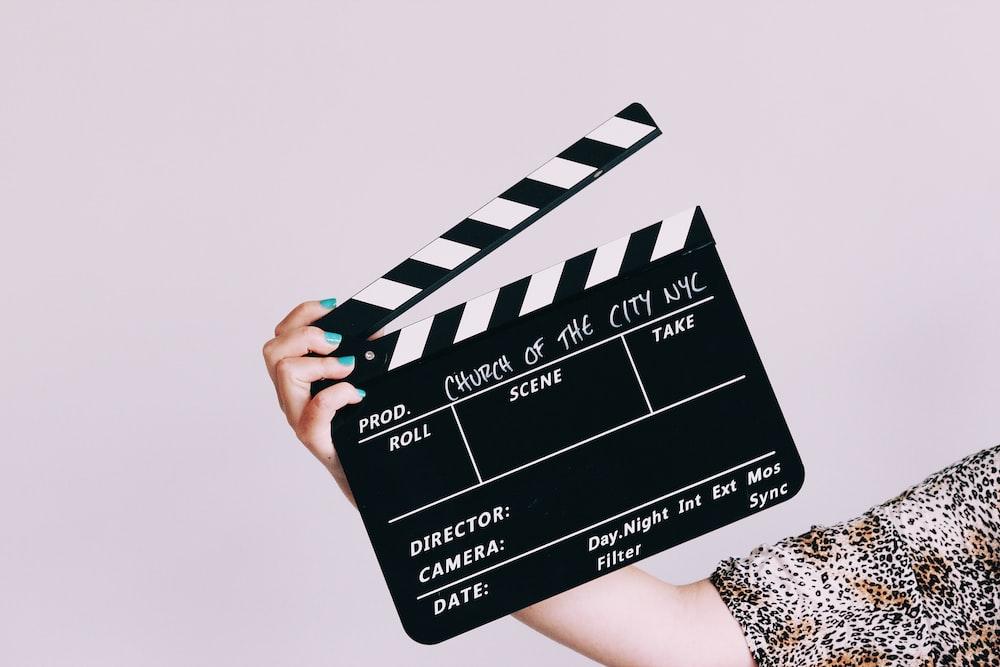 Eine Person hält eine schwarz-weiße Filmklappe.