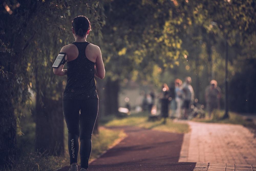 woman in black tank top and black pants walking on sidewalk during daytime