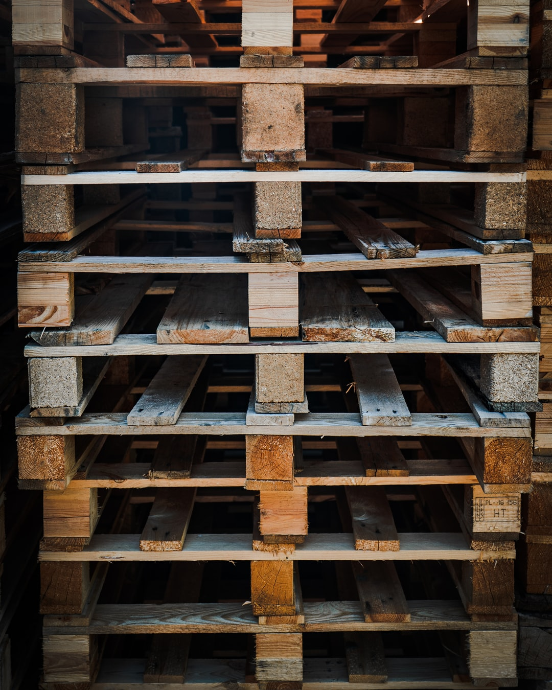 A pile of old, used pallets for transporting heavy goods in trucks, trains etc..