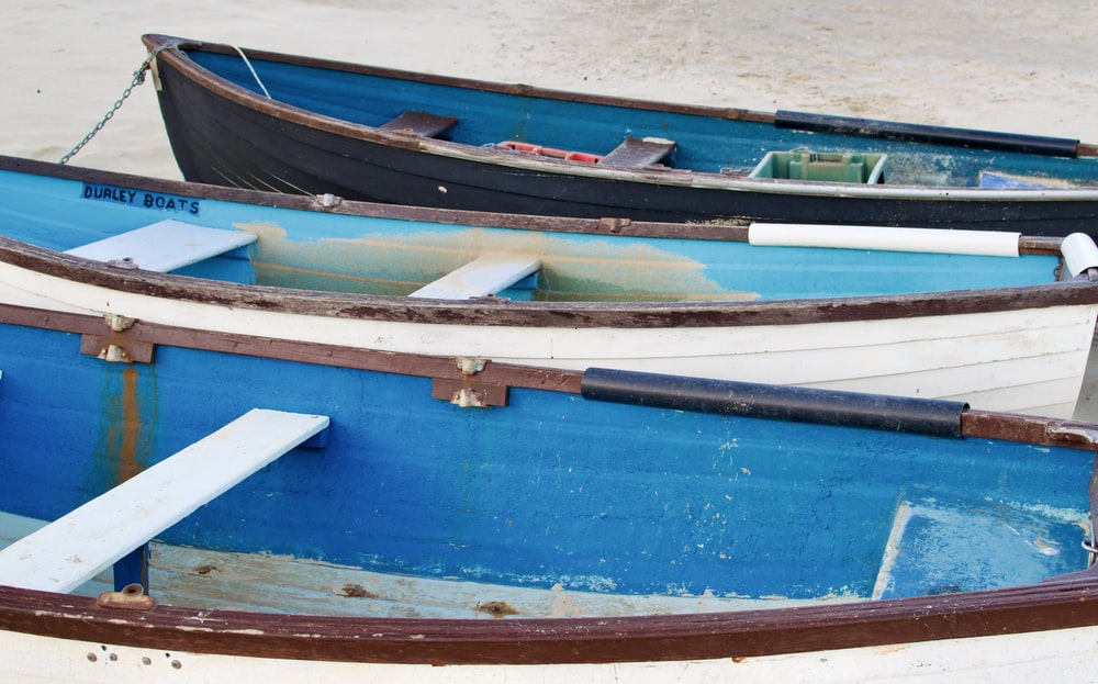blue and brown boat on white sand during daytime