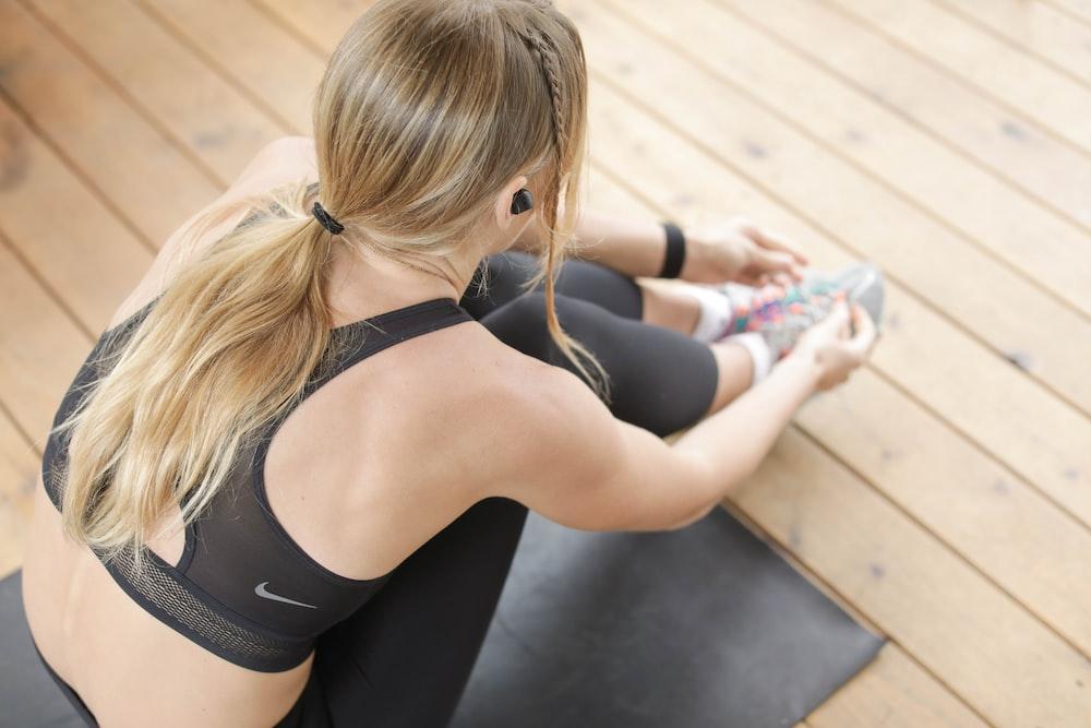 woman in black sports bra and black leggings sitting on brown wooden floor