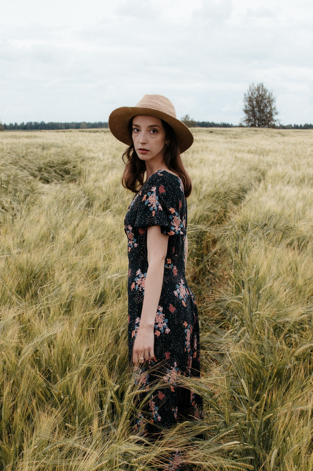 woman in black and white floral dress wearing brown straw hat standing on green grass field