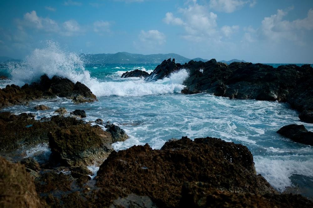 ocean waves crashing on brown rock formation under blue sky during daytime