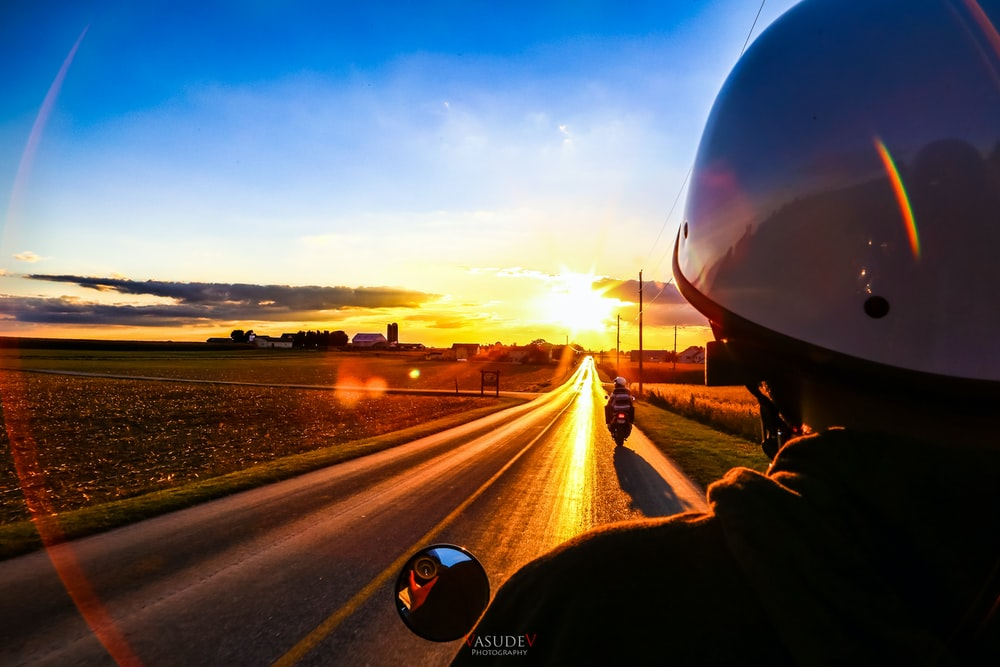 person driving car on road during sunset
