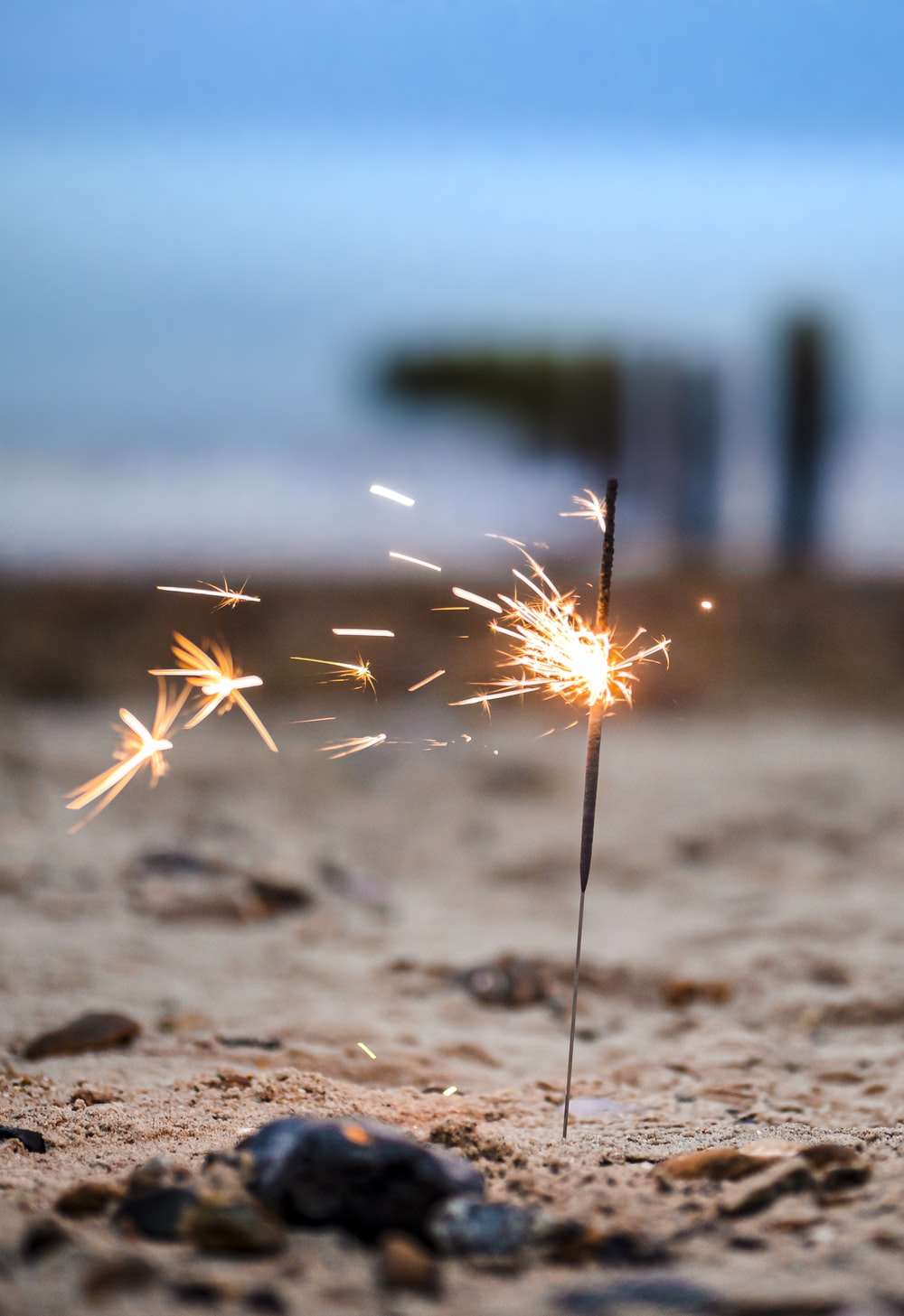 white and brown fireworks on brown sand during daytime