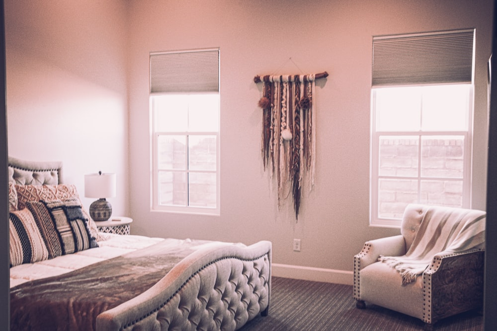 white bed near window with brown curtain