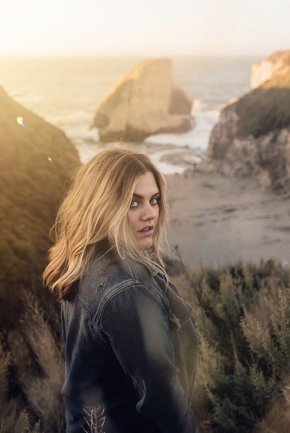 woman in black leather jacket standing near brown rock formation during daytime