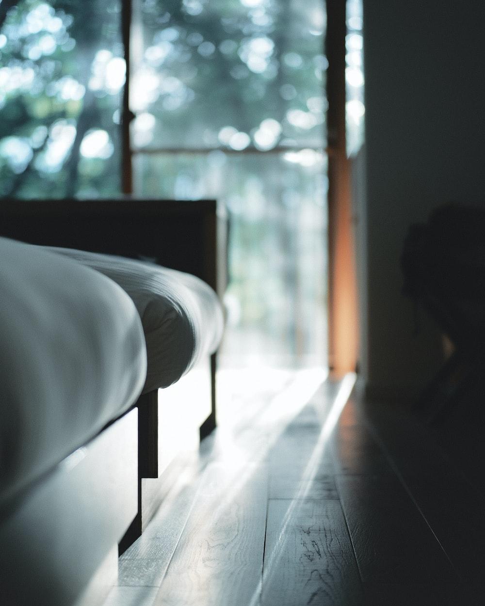 white bed near glass window