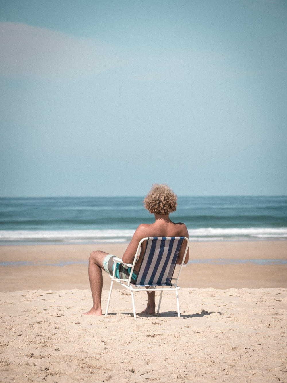 woman in red dress sitting on white and blue chair on beach during daytime