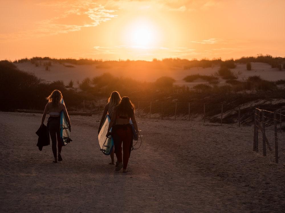 2 women walking on dirt road during sunset