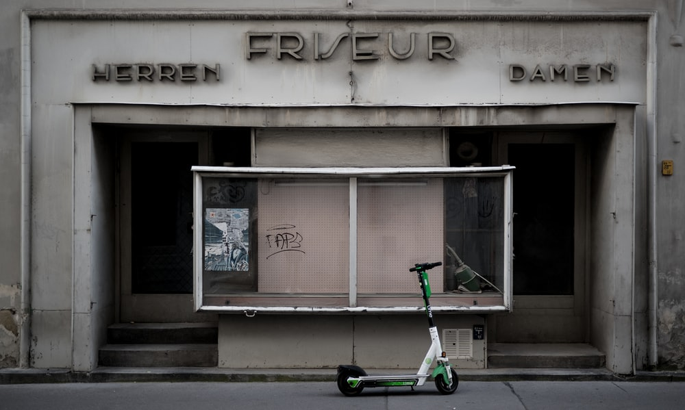 green and black bicycle parked beside the building