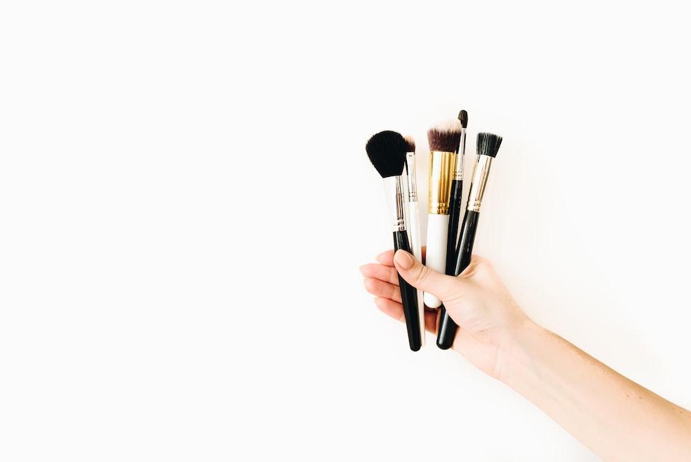 person holding black makeup brush