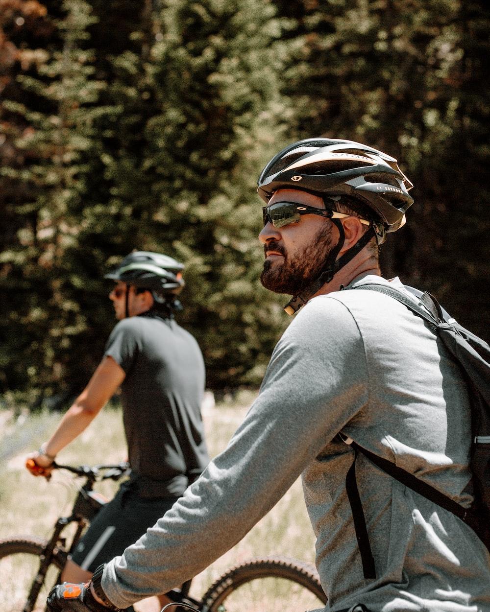 man in gray long sleeve shirt riding bicycle during daytime