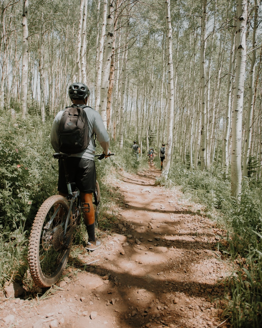 man in green jacket riding bicycle on dirt road during daytime
