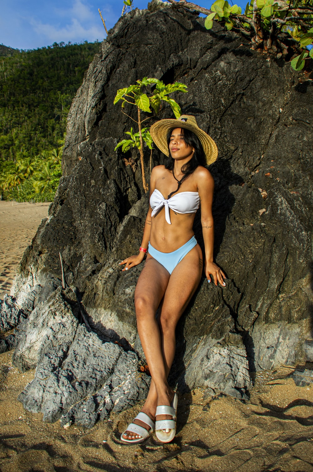 woman in blue bikini lying on rock