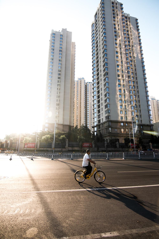 man in white shirt riding bicycle on road during daytime