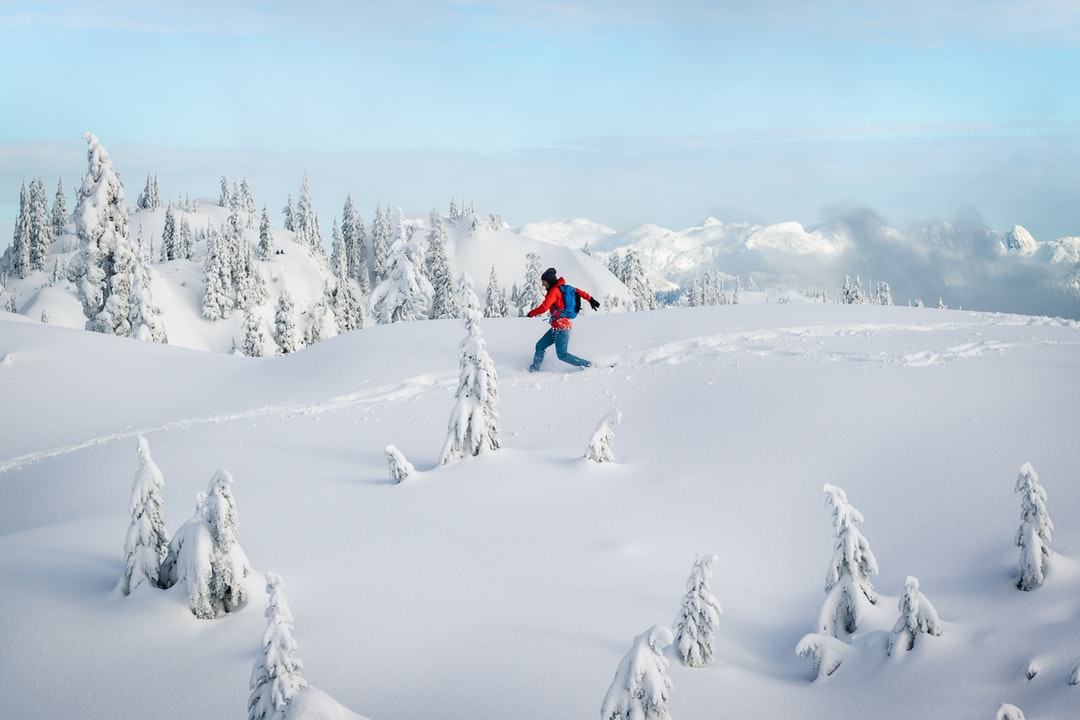 Woman snowshoeing in the snow covered mountains