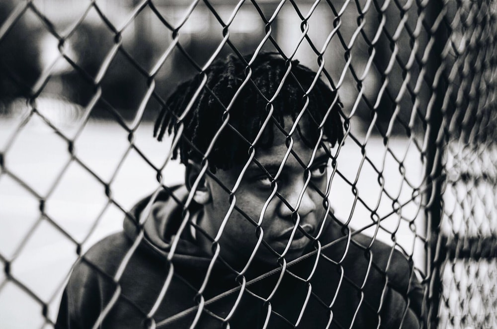 man in black jacket leaning on chain link fence