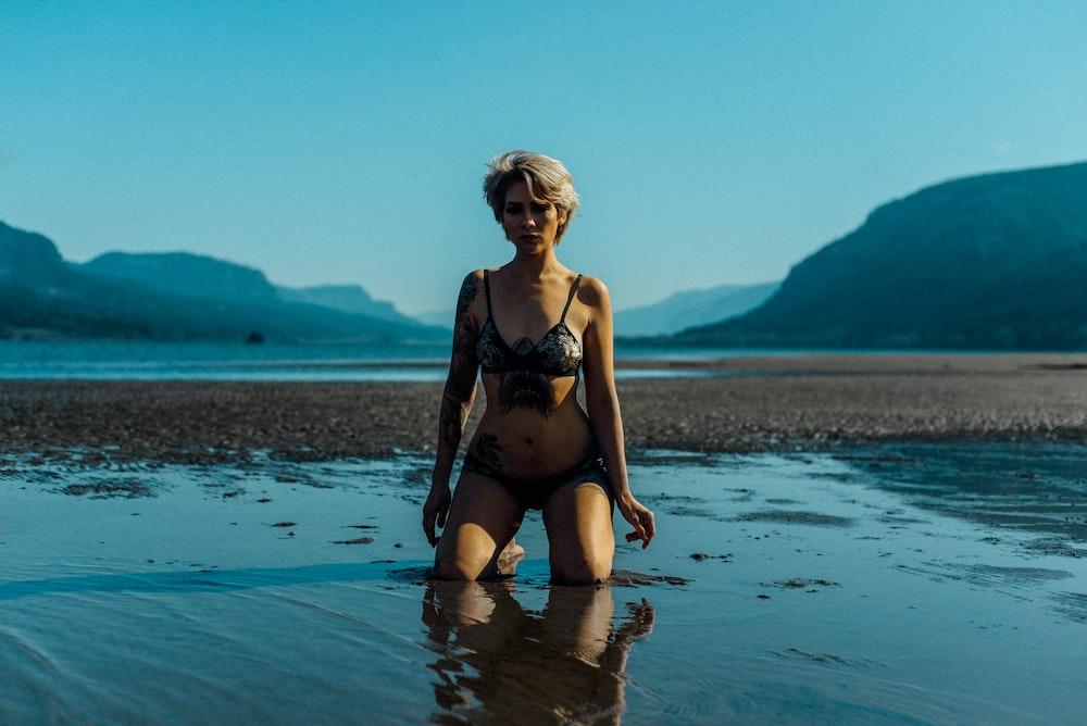 woman in black bikini standing on water during daytime