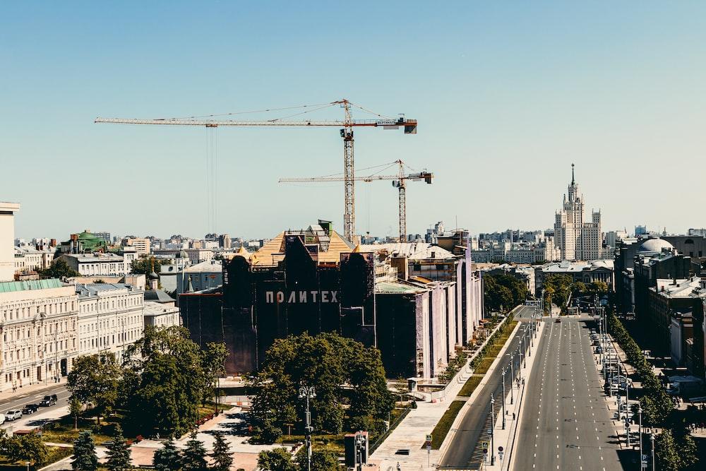 black and brown concrete building near gray concrete bridge under blue sky during daytime