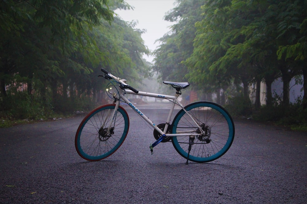 black and white road bike on road near green trees during daytime