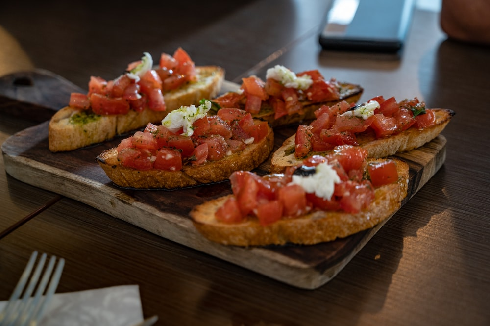 brown bread with tomato and green vegetable on brown wooden table