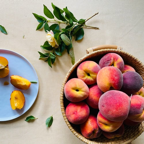 a basket full of peaches next to a plate with sliced peaches.