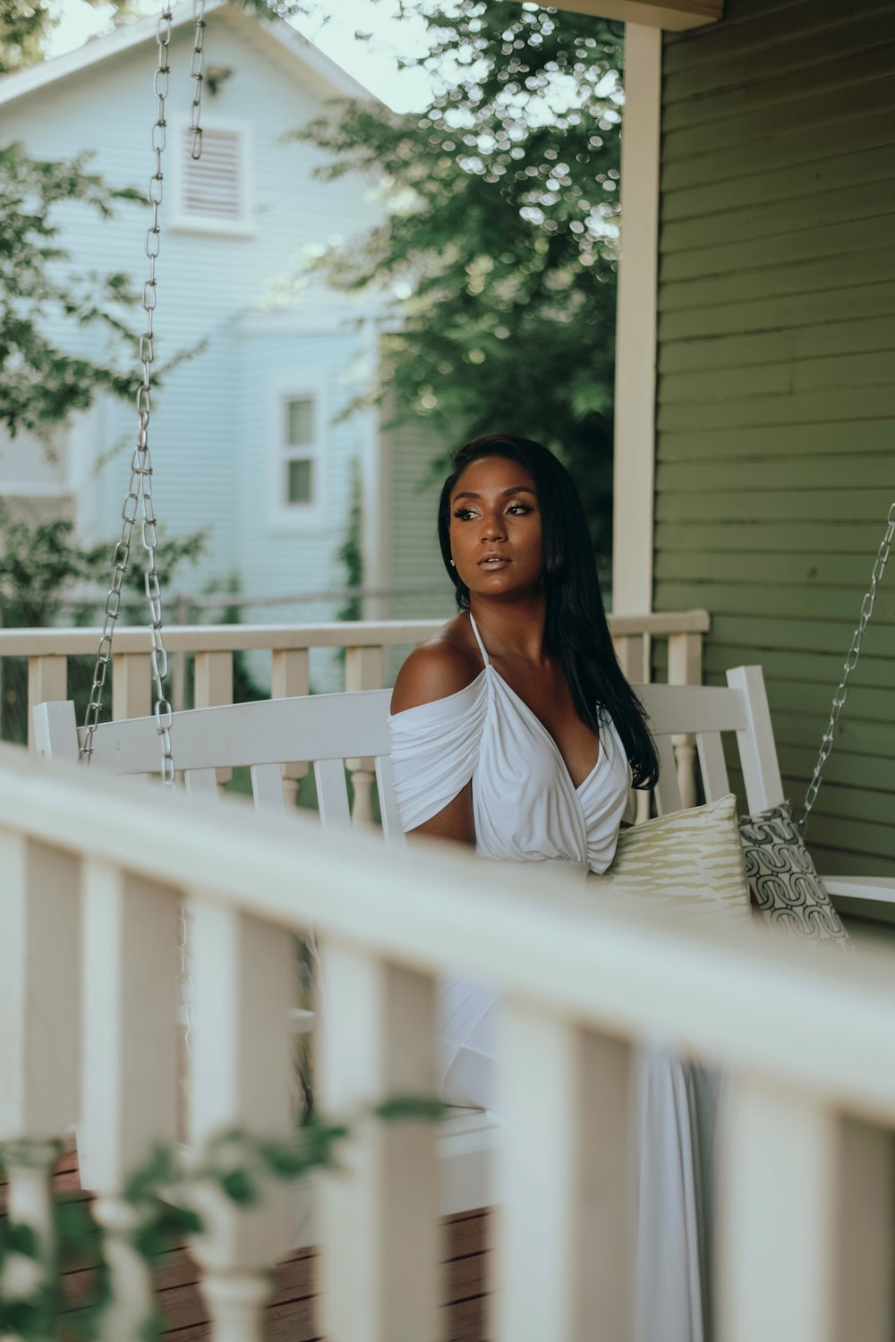 woman in white tank top standing on white wooden porch during daytime