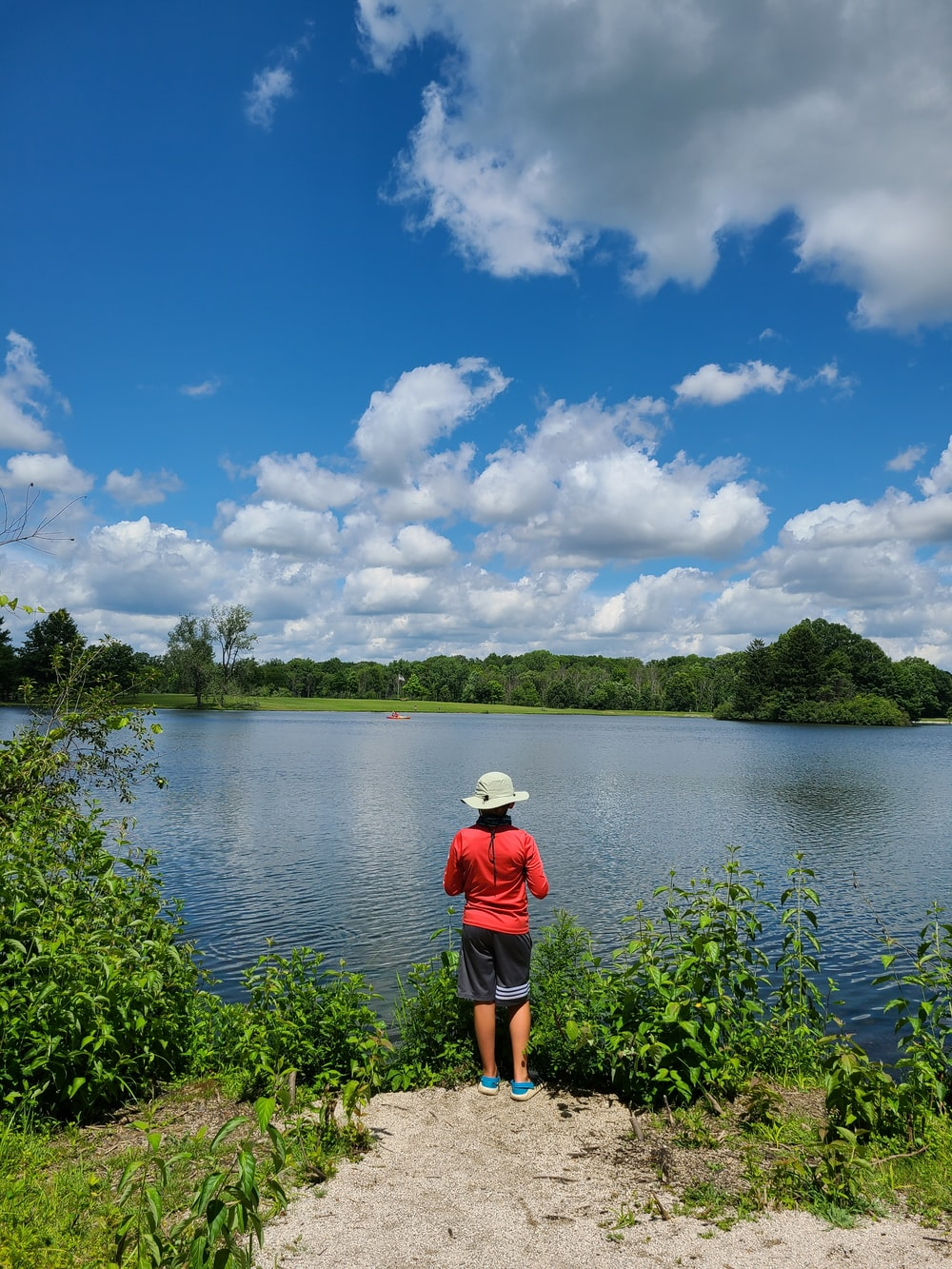 person in red shirt standing near lake during daytime