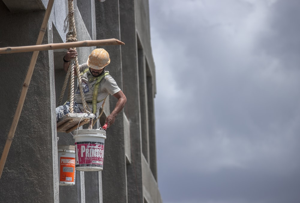 man in green t-shirt and brown hat climbing on gray concrete wall during daytime
