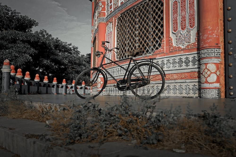 black city bike parked beside red building during daytime