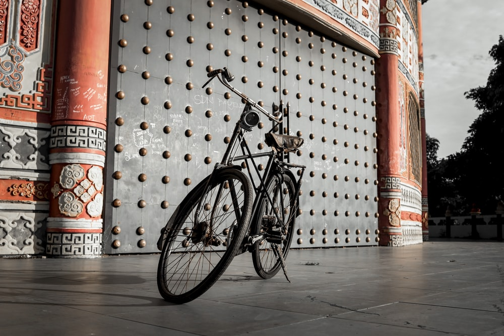 black city bike parked beside red and white wall