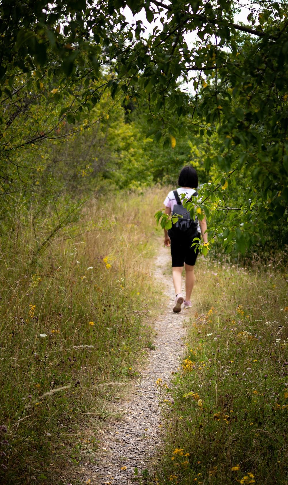 woman in black dress walking on green grass during daytime